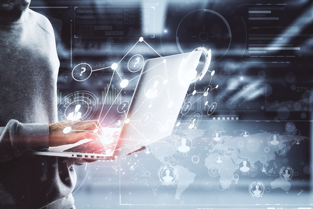 Hacker using laptop with digital business interface in blurry office interior. Hacking, future and network concept. Double exposure