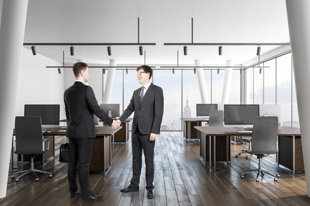 Attractive european businessmen shaking hands in modern office interior with city view and daylight. Teamwork and deal concept.