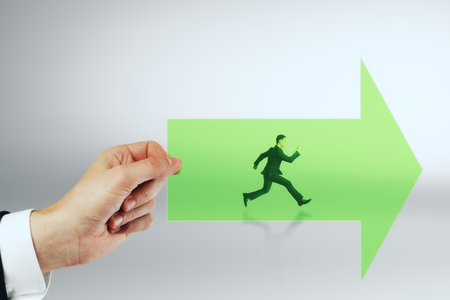 Hand holding green arrow with running businessman on grey background. Growth and success concept