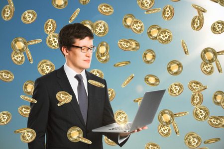 Businessman with laptop celebrating golden bitcoin rain on sky background. Cryptocurrency and finance concept