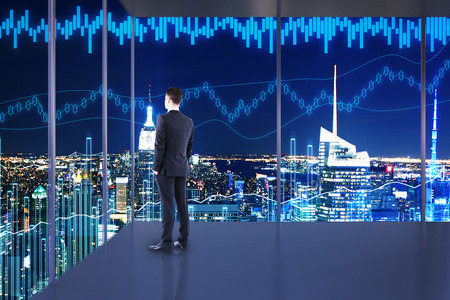 Trade and currency exchange concept. Businessman in interior with night NYC view and forex chart. Double exposure