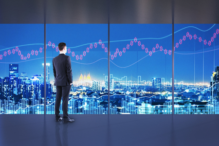 Trade and finance concept. Businessman in interior with night NYC view and forex chart. Double exposure Stock Photo