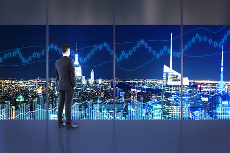 Trade and investment concept. Businessman in interior with night NYC view and forex chart. Double exposure Stock Photo
