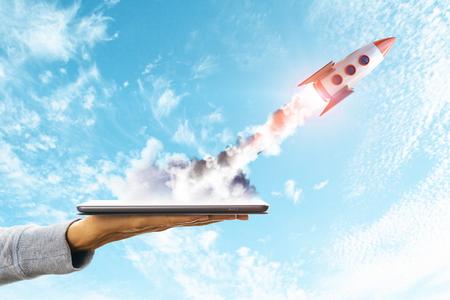 Mano que sostiene el teléfono inteligente con cohete de lanzamiento sobre fondo de cielo. Concepto de puesta en marcha y tecnología