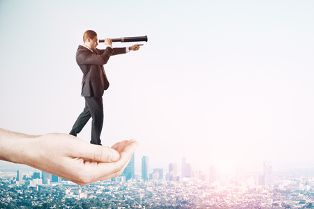 Vision and future concept. Hand holding businessman with telescope on sky background with copy space