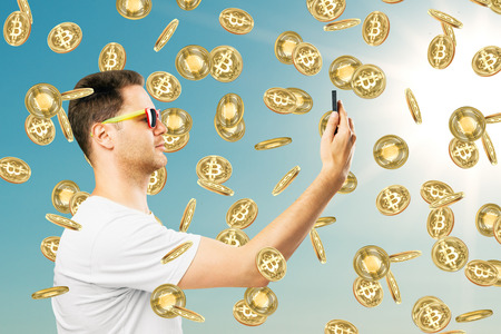 Young businessman with smartphone and bitcoin rain on sky background with siunlight. Success and income concept Archivio Fotografico - 115537730