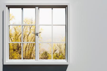 Modernes Fenster mit Landschaftsblick und Kopienraum auf Betonwand. Haus- und Designkonzept. 3D-Rendering Standard-Bild