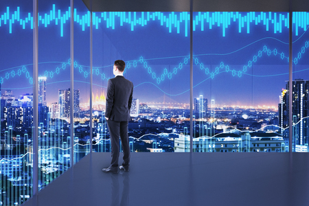 Trade and profit concept. Businessman in interior with night NYC view and forex chart. Double exposure  Stock Photo