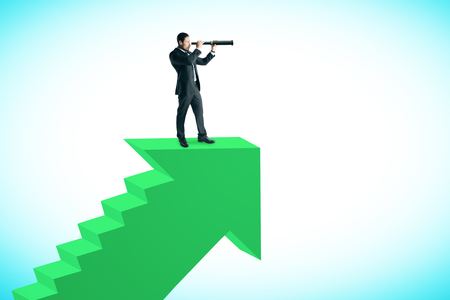 Young businessman on top of abstract green arrow ladder on sky background. Career promotion and vision concept.