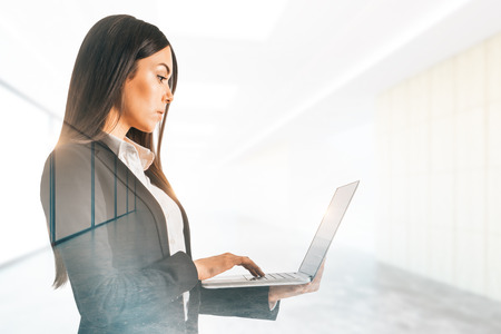 Side view of attractive young woman using laptop in blurry office interior. Technology and communication concept. Double exposure