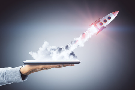 Hand holding smartphone with launching rocket on dark background. Startup and technology concept