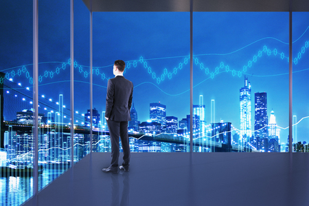 Trade and market concept. Businessman in interior with night NYC view and forex chart. Double exposure