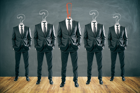 Row of question and exclamation mark headed businessmen standing in abstract chalkboard interior. Leadership and teamwork concept