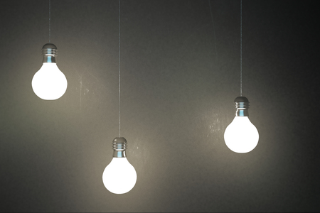 Glowing light bulbs on concrete wall background. Idea and innovation concept. 3D Rendering Reklamní fotografie