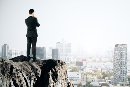 Back view of young businessman looking at city from cliff. Future and research concept