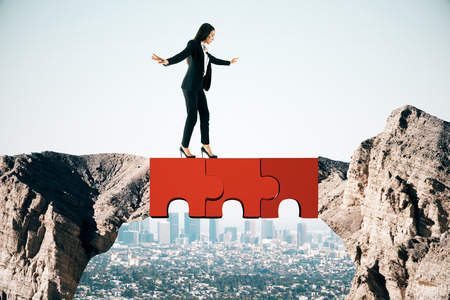 Jeune femme d'affaires traversant le pont de puzzle abstrait sur fond de ciel. Concept de travail d'équipe et d'équilibre