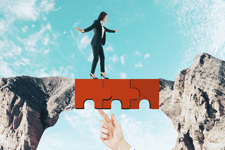 Young businesswoman crossing abstract jigsaw bridge on sky background. Teamwork and challenge concept 写真素材 - 116139190