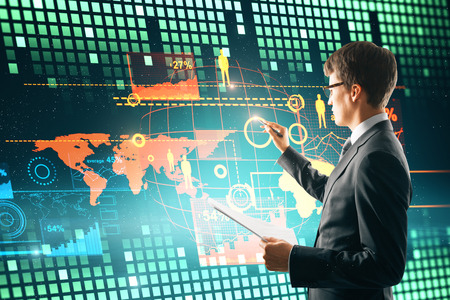 Attractive young businessman using digital business interface. Innovation and hud concept.