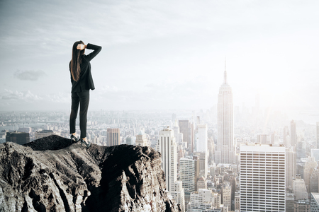 Back view of young businesswoman looking at New York city from cliff. Future and research concept Imagens