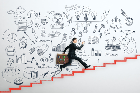 Side view of young businessman with travel briefcase running up drawn stairs on concrete wall with creative business sketch. Success and workshop concept 版權商用圖片