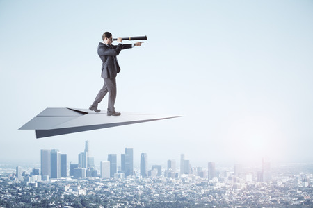 Young businessman using telescope to look into the distance while standing on paper plane on sky and city background. Research and direction concept Stok Fotoğraf