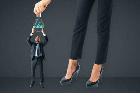 Businesswoman hanging lamp to tiny businessman on gray background. Teamwork and idea concept Stock Photo
