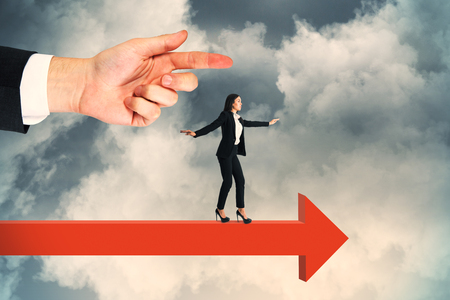 Side view of hand pointing at attractive young european businesswoman balancing on red arrow. Cloudy sky background. Challenge and risk concept 스톡 콘텐츠