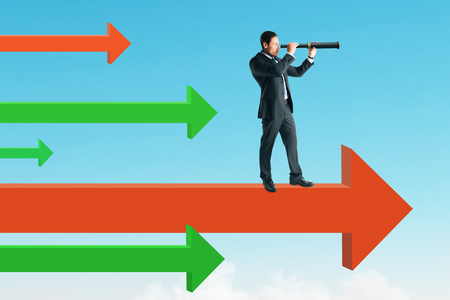 Side view of young businessman looking into the distance while standing on arrows. Sky background. Vision and success concept