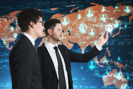Two handsome young businessmen with abstract map interface. Global business and communication concept. Stockfoto