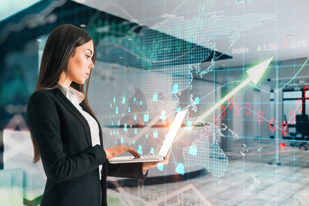 Trade and investment concept. Side view of attractive young businesswoman using laptop in modern office interior with forex chart and upward arrow. Double exposure