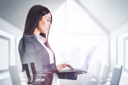 Side view of attractive young businesswoman using laptop in blurry office interior. Technology and communication concept. Double exposure