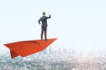 Young businessman looking into the distance while standing on red paper plane. Sky and city background. Freedom and vision concept