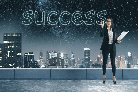 Young businesswoman writing abstract success word on concrete rooftop background with blurry night city view. Successful female concept