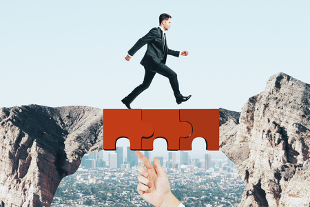Young businessman crossing abstract jigsaw bridge on sky background. Teamwork and solution concept Imagens