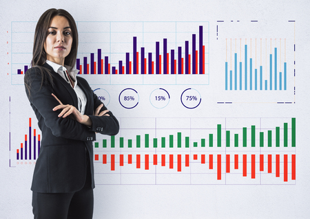 Attractive young businesswoman standing on concrete wall background with business charts sketch. Finance and economy concept Banco de Imagens - 117202054