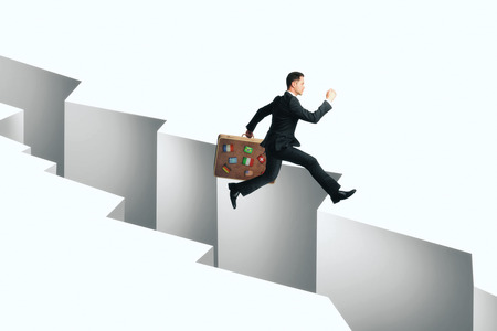 Businessman with travel suitcase jumping over gap. Obstacle overcoming concept