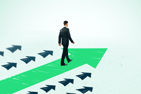 Side view of young businessman following drawn arrows on light background. Success and leadership concept