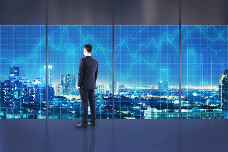 Businessman standing in abstract interior with night New York city view and forex chart. Office and broker concept.