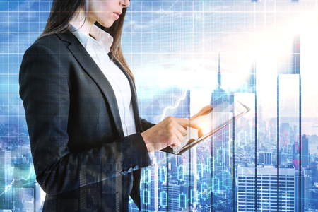 Side view of attractive young businesswoman using laptop on abstract New York city background with forex chart. Broker and trade concept. Double exposure Stock Photo