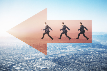 Side view of young businessmen running on red arrow on city background with daylight. Direction and teamwork concept Stock Photo