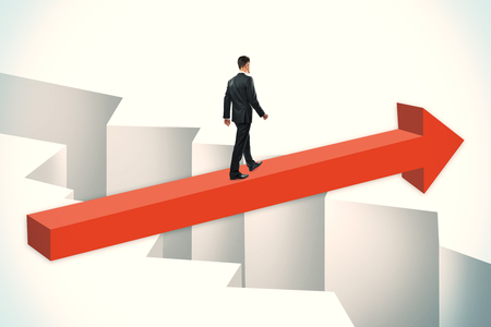 Businessman walking on red arrow over gap. Challenge and overcoming problems concept. Stock Photo