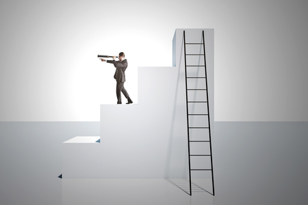 Businessman looking into the distance on top of stairs with ladder on white background. Vision and growth concept.