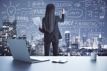 Back view of young businesswoman drawing creative business sketch on abstract city background with charts on laptop screen and coffee cup. Report and finance concept Stock Photo