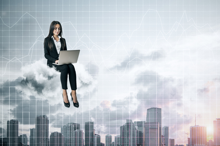 Attractive young businesswoman using laptop while sitting on cloud with forex chart on sky and city background. Cloud computing and trade concept