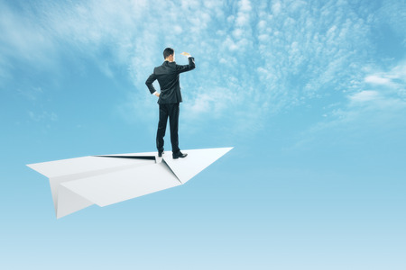 Young businessman looking into the distance while standing on white paper plane. Sky and clouds background. Freedom and research concept