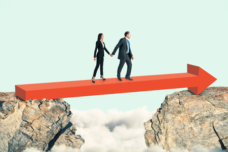 Side view of young businessman and woman walking over red arrow between two cliffs on sky background. Challenge and teamwork concept  Banco de Imagens