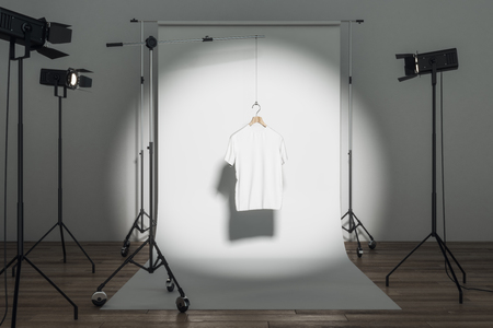 Empty white tee in photo studio with professional lighting equipment. Fashion, design and mockup concept. 3D Rendering