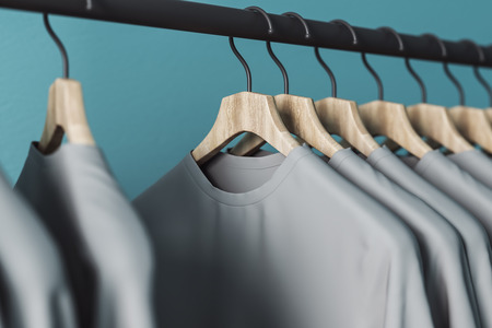 Row of grey tees on hangers. Blue wall background. Style and design concept. 3D Rendering