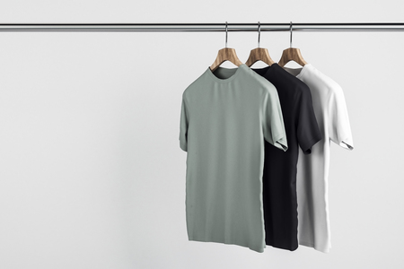 Empty grey, white and black tees on hanger. Concrete wall background. Design, store and style concept. Mock up, 3D Rendering Archivio Fotografico