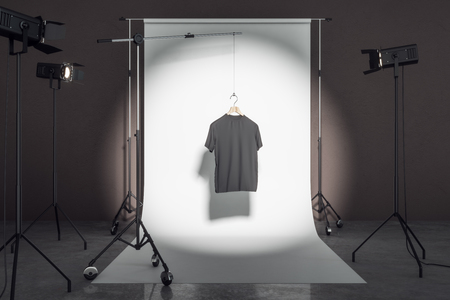 Empty black tee in photo studio with professional lighting equipment. Fashion, design and mockup concept. 3D Rendering